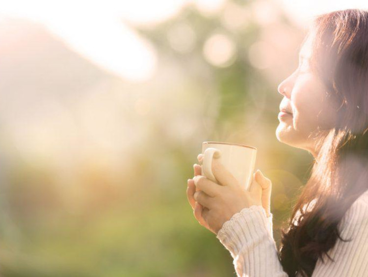 woman holding a coffee cup outside