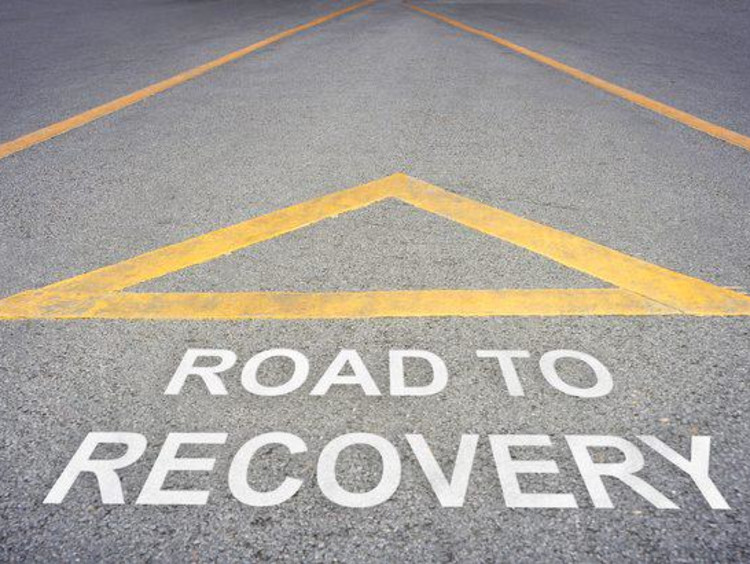 Yellow upright triangle above road to recovery lettering on a road