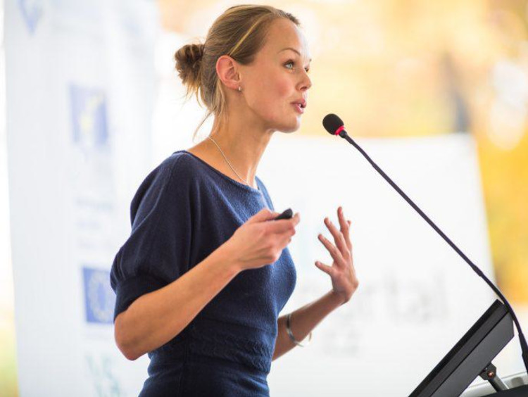 Adult woman speaking into microphone