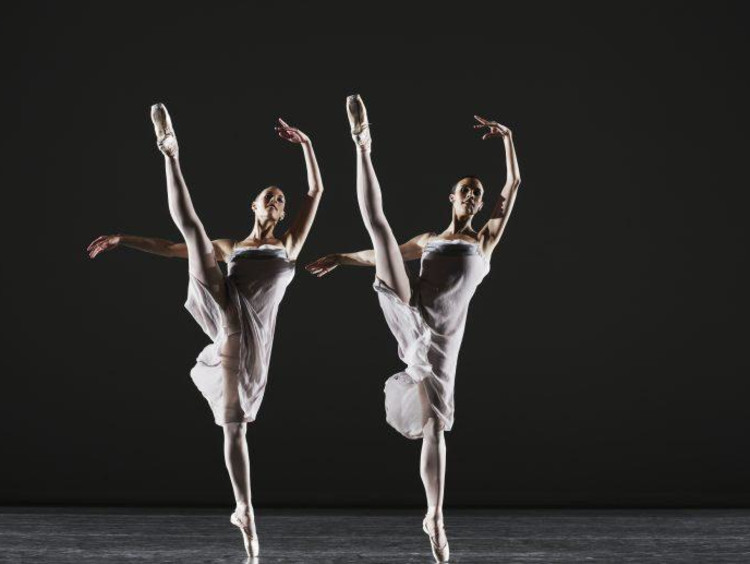 Two ballerinas dancing on stage, legs raised