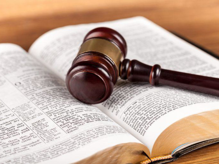 open bible with gavel sitting on top of it
