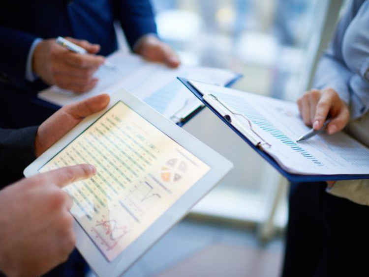 Trio of business professionals compare analytical graphs