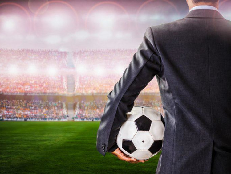 Businessman holds a soccer ball looking out at the field and a filled stadium