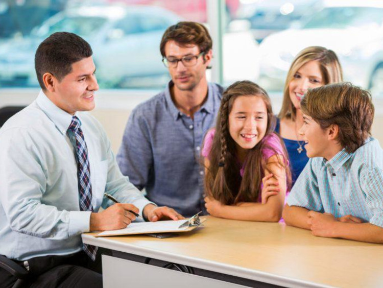 Guy with clipboard sits in front of two eager kids with parents in background