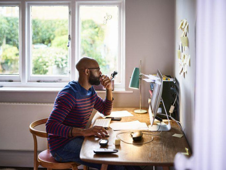 Man at desk by window with computer