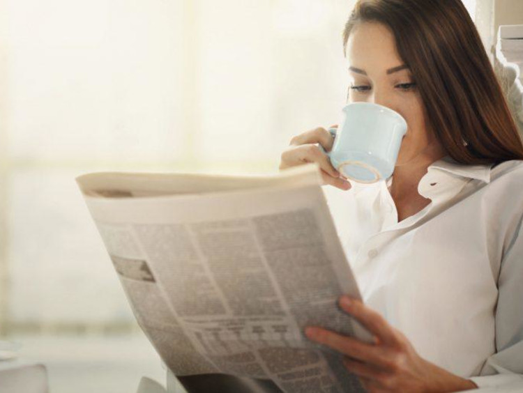 girl reading newspaper and sipping out of a mug