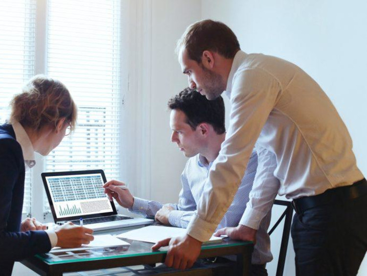 Business analyst shows two other professionals a data discrepancy on screen