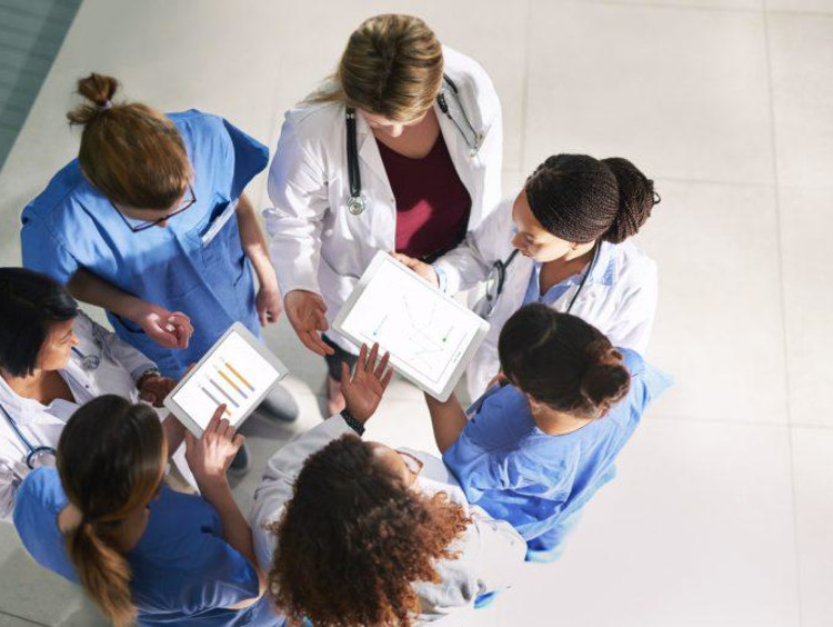 A team of nurses standing in a circle with their hands placed in the center.
