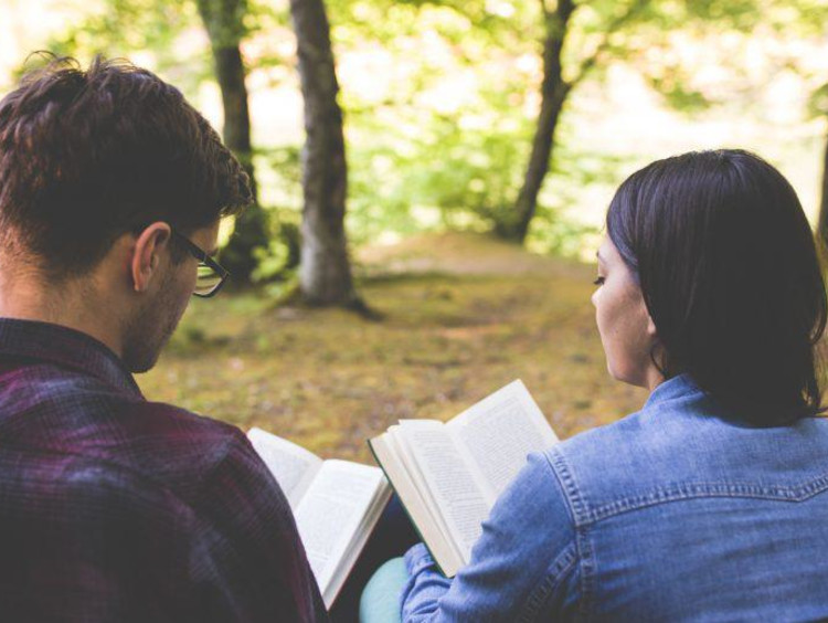 Two young adults reading scripture together.