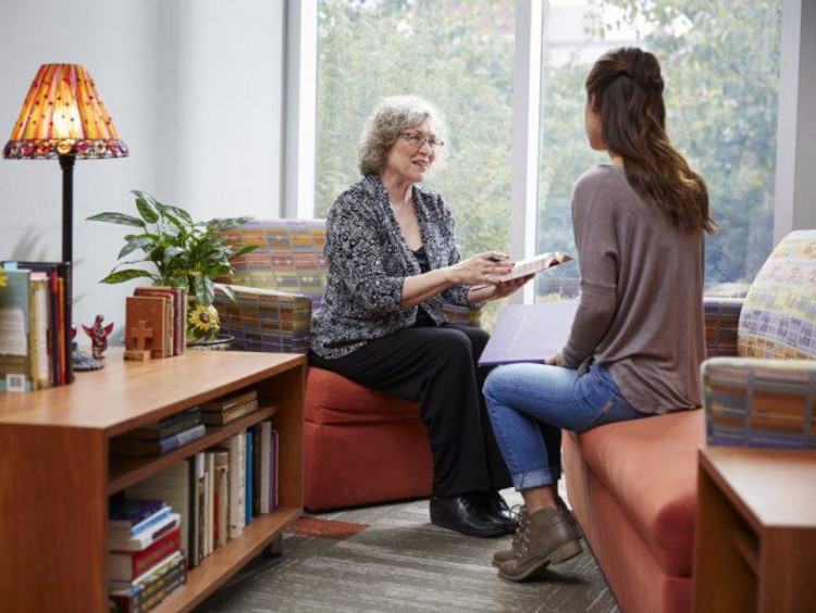 Older woman shares Bible reference with younger female sitting across from her