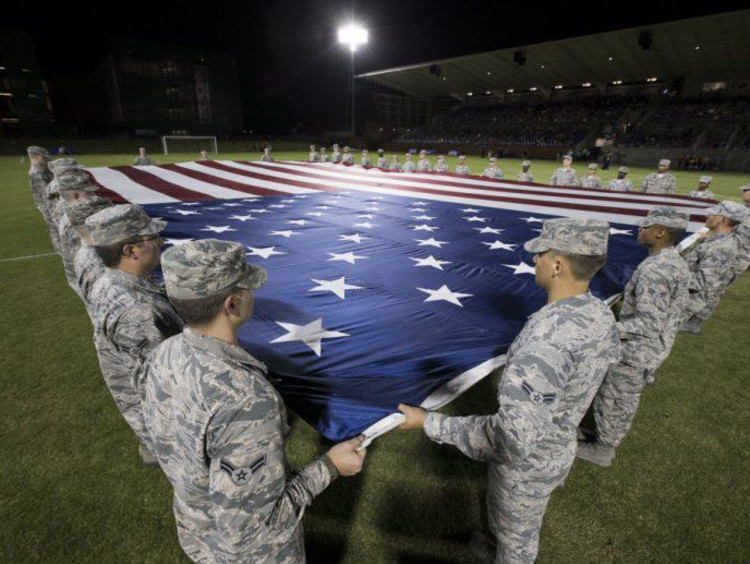 Military members holding the flag
