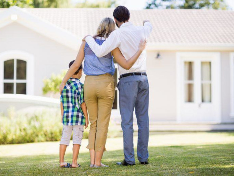 family hugging and looking at a house