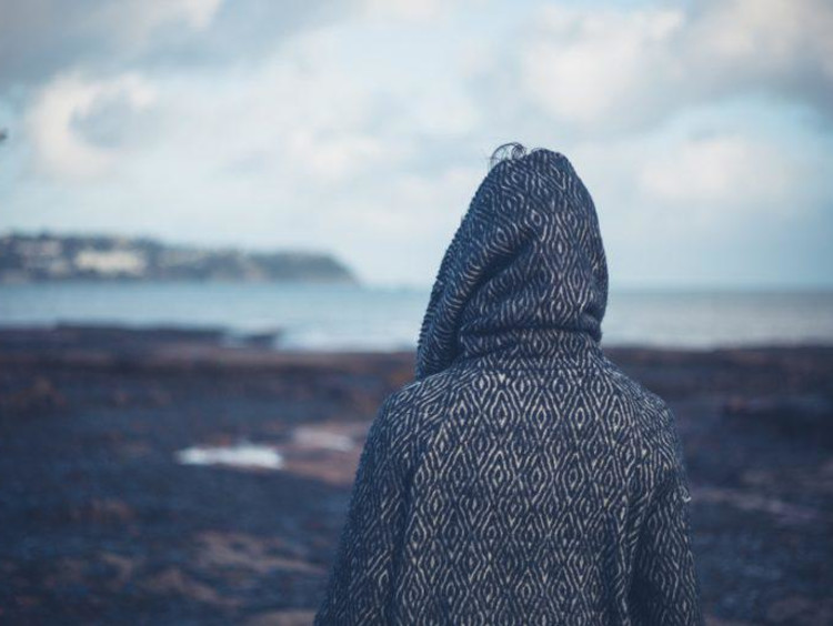 Back of hooded individual looking out at a barren landscape