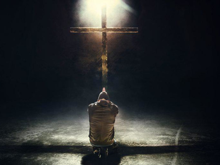 person kneeling and praying at the cross