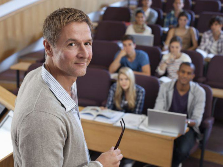 Male instructor stands next to podium with a full auditorium of students