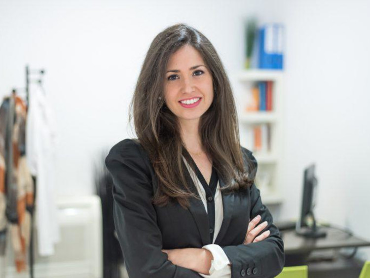 Young professional counselor stands in her office with arms crossed while smiling