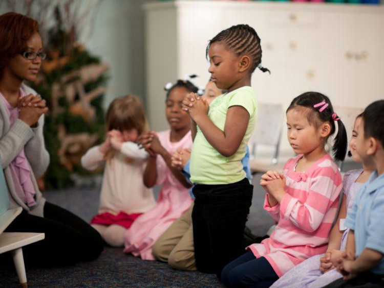 children praying in a class