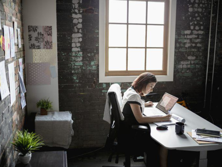 Woman sitting at desk in office next to window