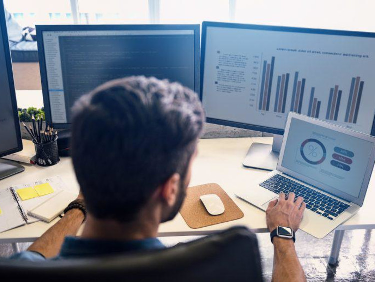 woman looking at computer of statistics
