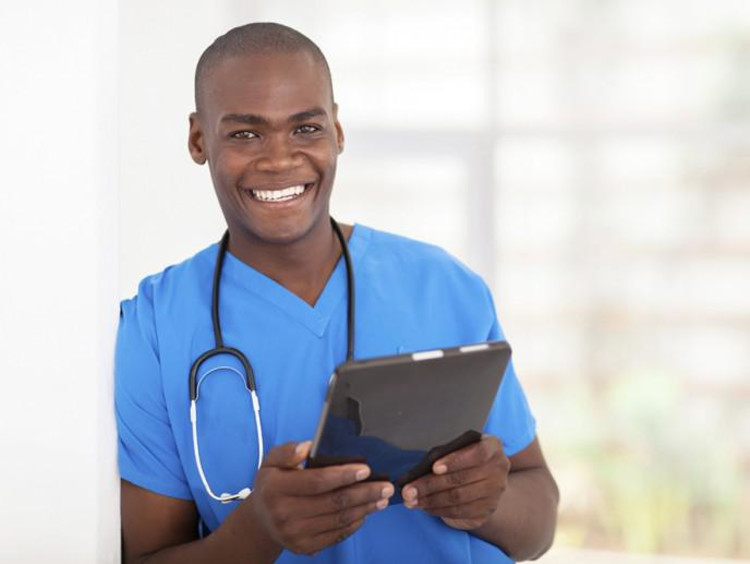 male nurse holding clipboard and smiling