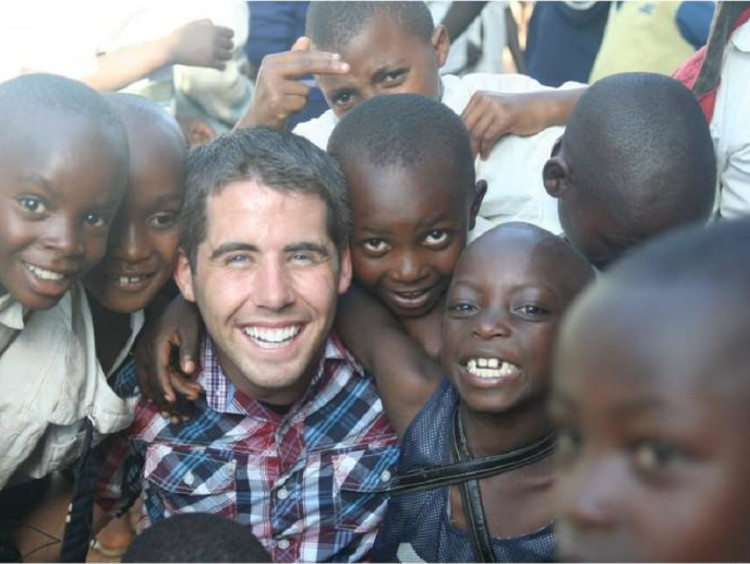 A man surrounded by a group of happy children
