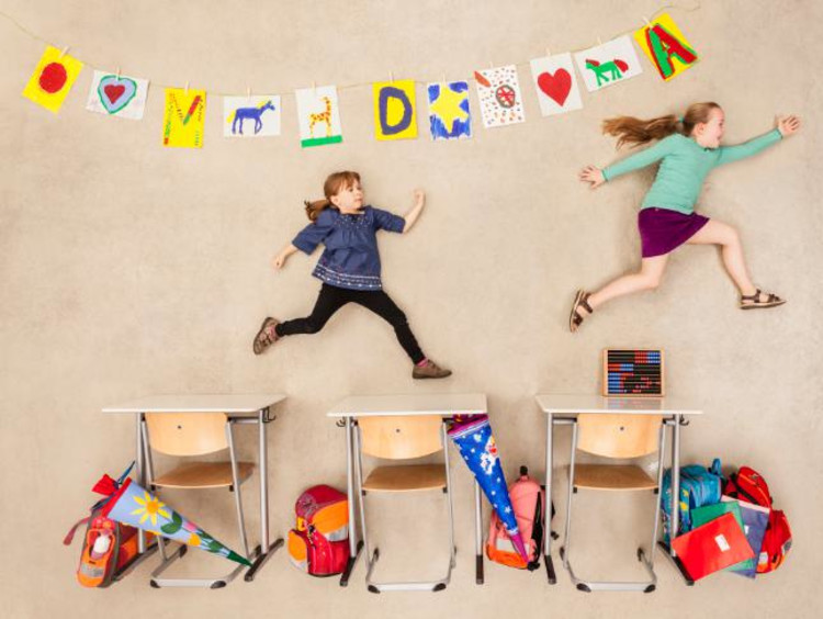 Two girls jump over desks next to a wall