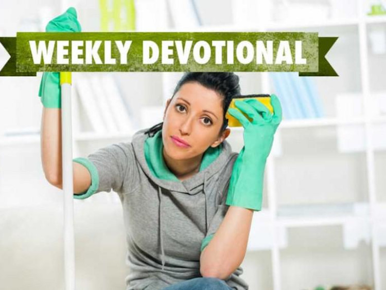 Woman wearing cleaning gloves looks tired with sponge in hand
