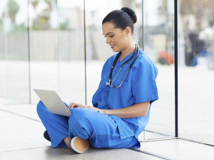 nurse sitting on floor typing on a laptop
