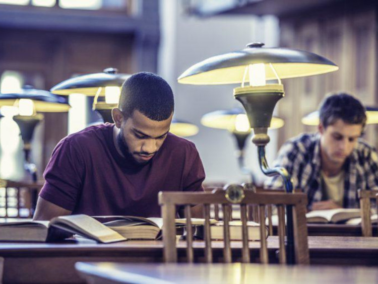 Two male students are focused on reading in a library
