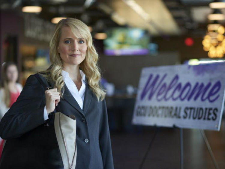 Blonde woman in professional clothing stands at entrance for doctoral studies mixer