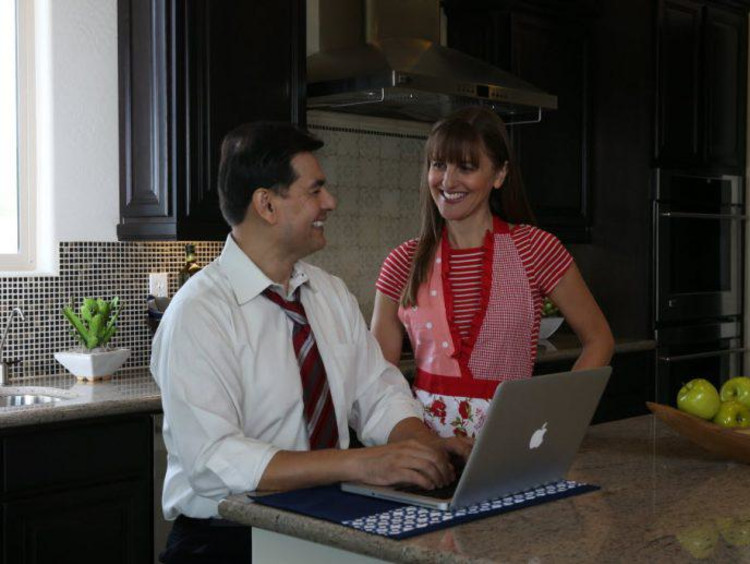 Husband uses laptop in kitchen and wife in apron talks to him