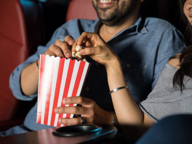 two people eating popcorn at the movies