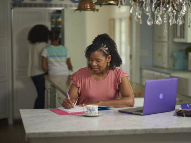 A woman taking notes at her kitchen table