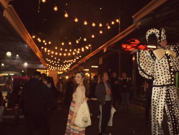 Kaitlyn stands in the middle of a busy Melbourne marketplace at night