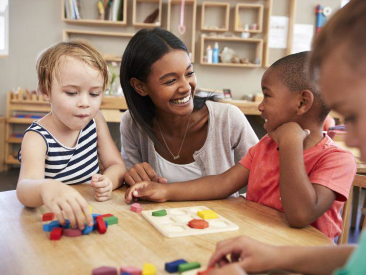 Teacher smiling helping little kids