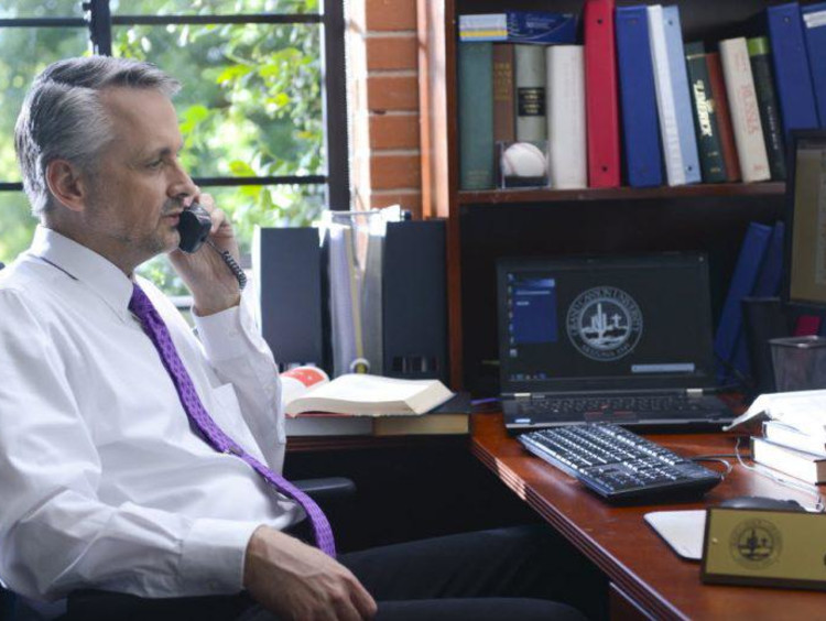 Doctoral education leader speaks on the phone in his office