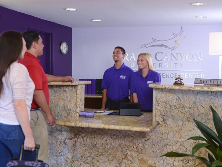 Couple checks in at the GCU Hotel reception desk