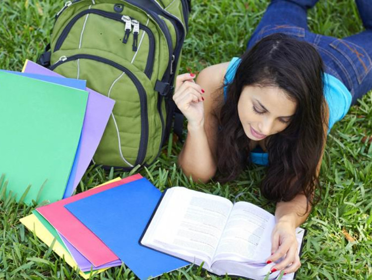 A student reading her notes outside in the grass