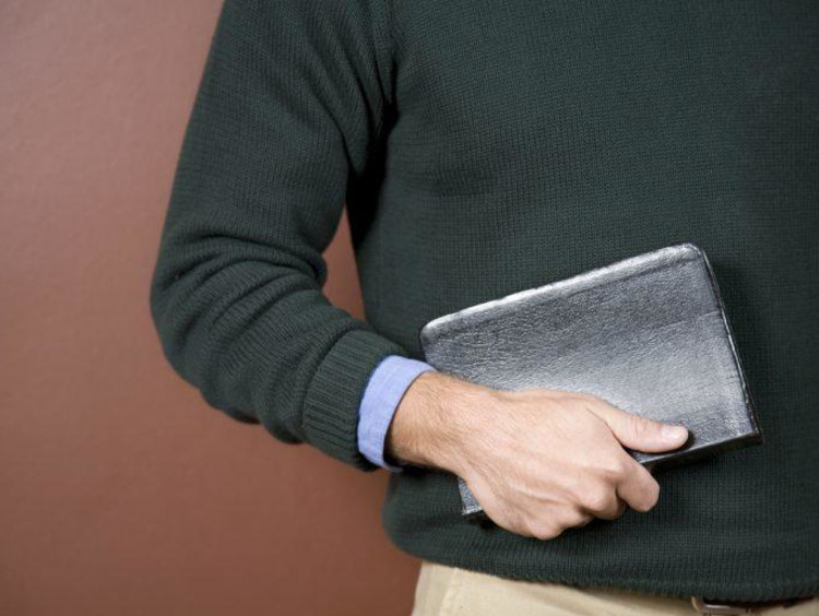 close up of man holding his Bible