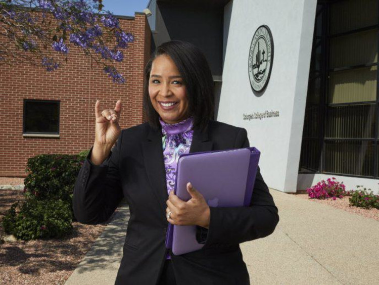 Adult MBA student gives a Lopes Up sign outside college of business building