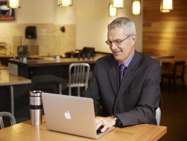 Older businessman uses laptop in empty coffee shop