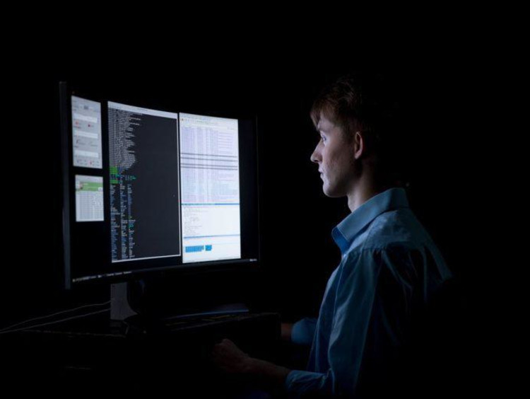 Computer programmer working in the dark