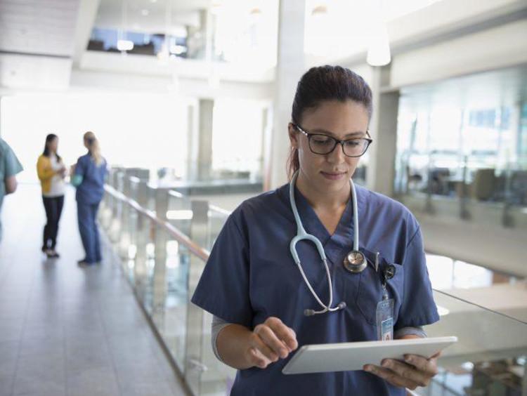 nurse looking at clip board