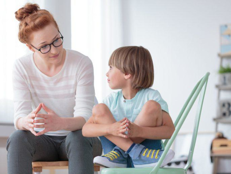 Female behavioral health counselor sits with young boy in play room