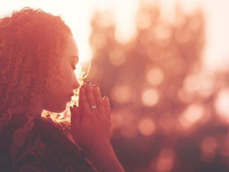 woman praying in the sunlight