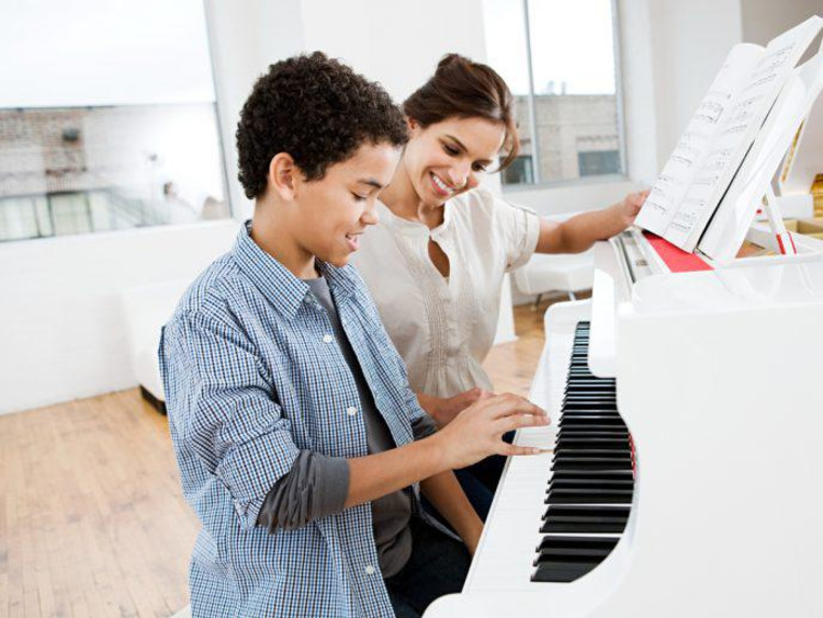 woman teaching piano to a child