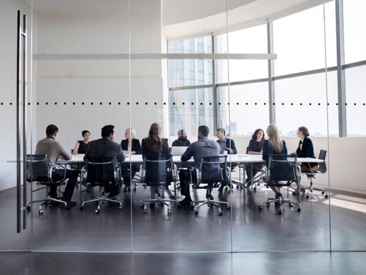 Business meeting takes place in glass wall conference room