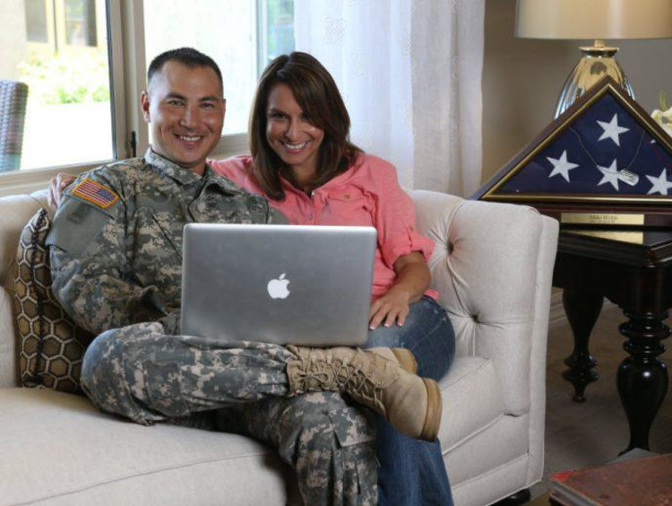 A veteran sitting with his partner in their home