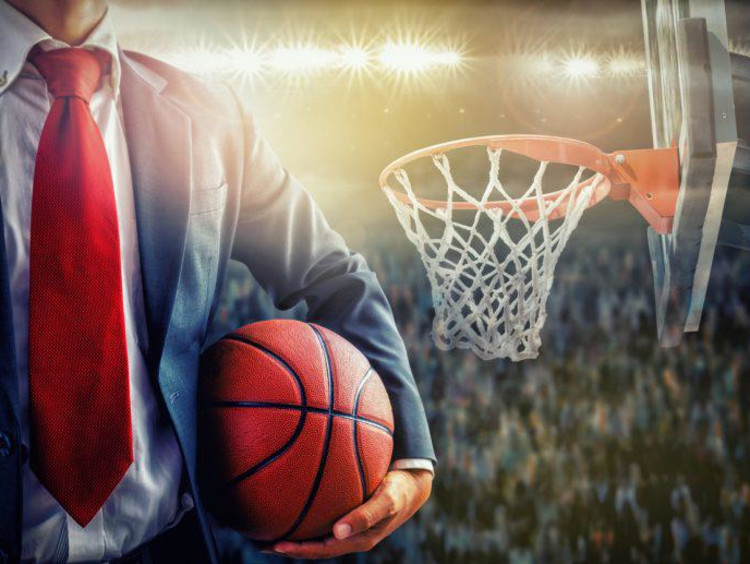 Businessman holds a basketball in a full arena