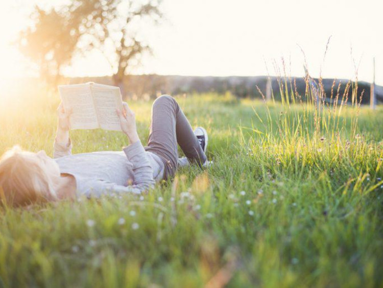 Woman lays in the grass and reads a book